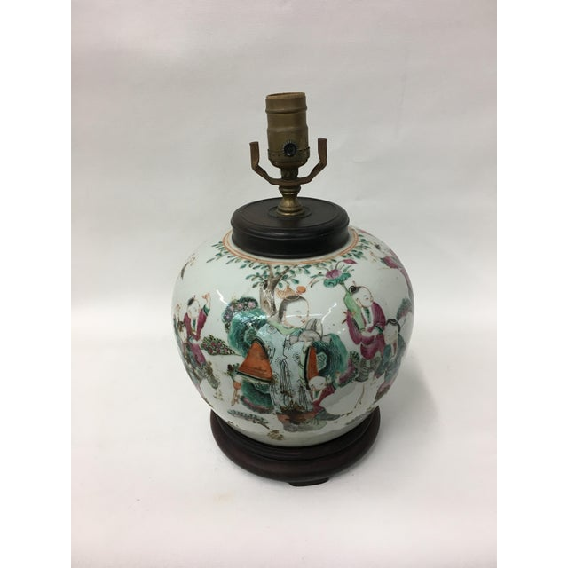 Chinese style ginger jar lamp shows children from court decadently dressed in bright colored robes playing together and...