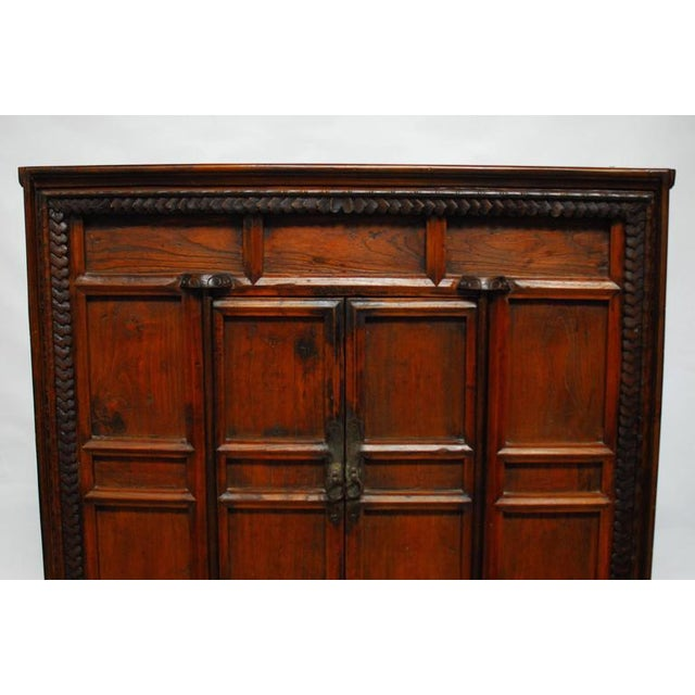 Large, Chinese two-door cabinet chest with a decorative carved front case featuring a Jacobean style border and a faux...