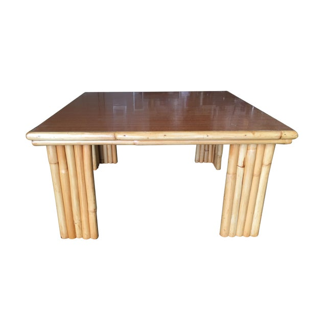 Extra wide square coffee table with pole rattan legs and a Formica wood grain pattern top with a rattan trim along the...