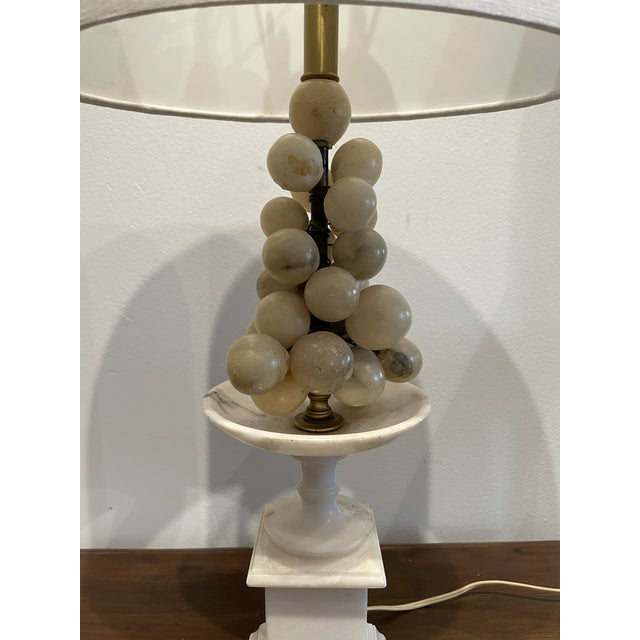 A whimsical and stylish marble vase with alabaster grape accents and a linen shade.