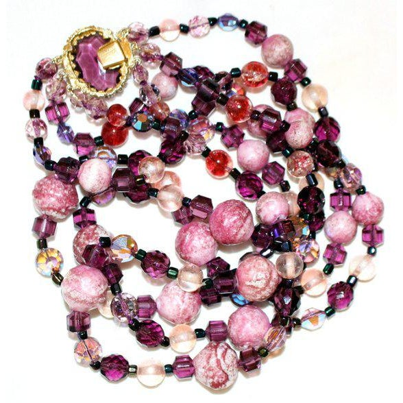 Gorgeous pink and purple 1950s to 1960s three strand necklace with multi color, shape and size glass beads with a goldtone...
