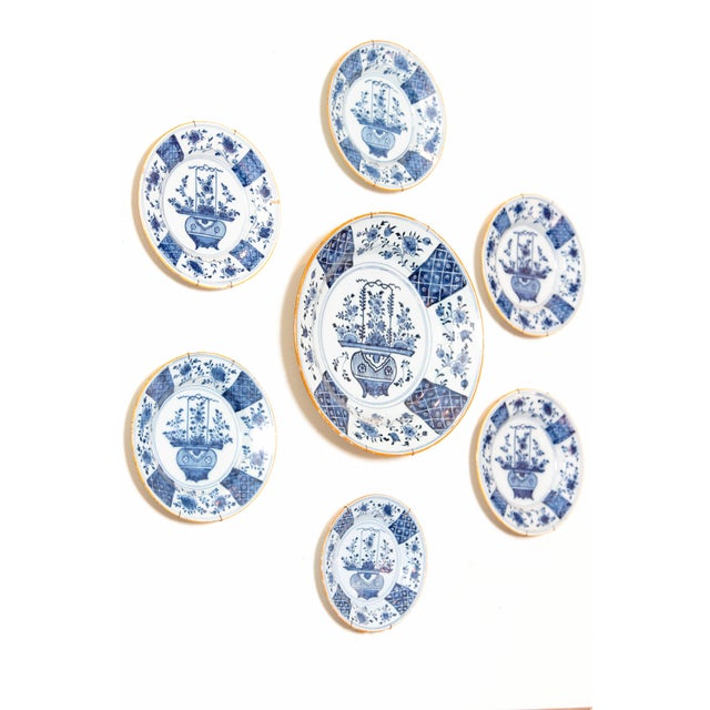 group of seven blue and white Delft plates with Chinese Flower Basket decoration, both 18th and 19th centuries, marked on...