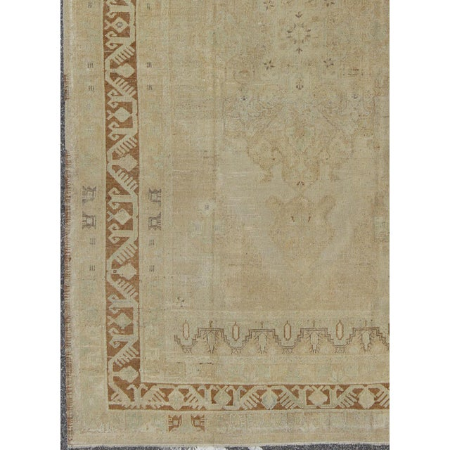 Characterized by a comely and highly representative Oushak composition, this vintage Oushak carpet beautifully...