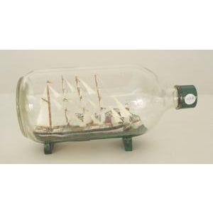 American/English (19/20th Cent) sailing ship with 4 masts and a light house in a bulbous shaped glass bottle on a green...