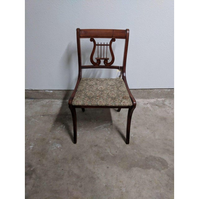 A grouping of six lyre back dining chairs. This collection includes one head of table chair and five side chairs. The...