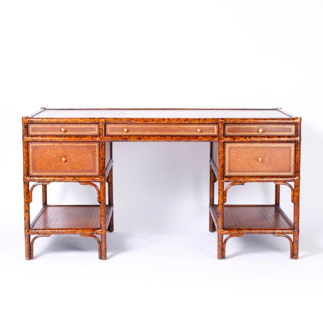 Midcentury kneehole five-drawer desk with a faux tortoise frame featuring a paneled and tooled leather top, drawer fronts,...