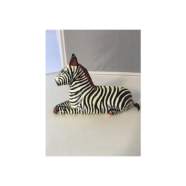 Papier-mâché reclining zebra. Zebra is signed on the base in paint.