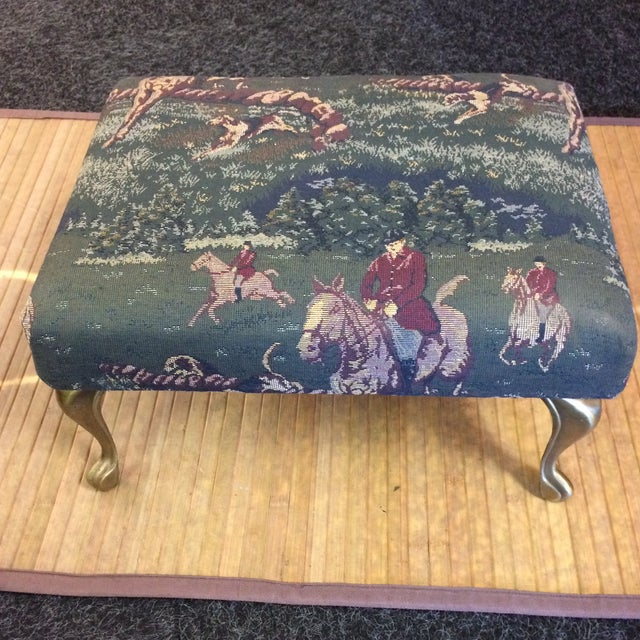 Wonderful small foot stool. Has metal gold tone finished legs. The fabric is an English Hunting Scene with Horses and Riders.