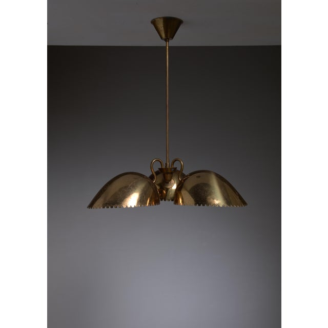 A wonderful brass pendant from Sweden by Bertil Brisborg for Bohlmarks. The lamp has three shades with serrated and...