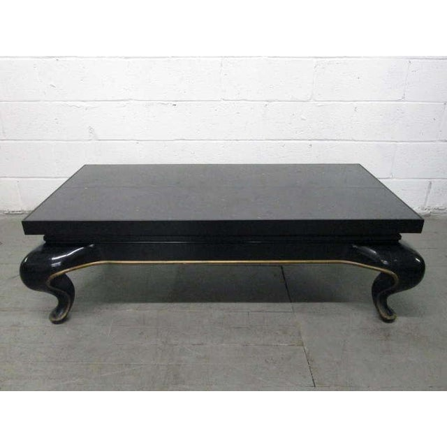 Asian slate top coffee table in the manner of James Mont. Black lacquered and gold trimmed base with a slate top.