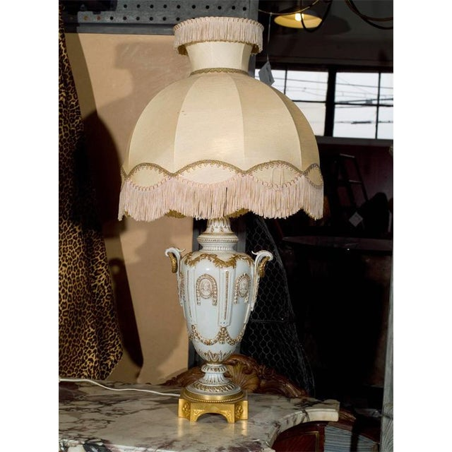 Fabulous pair of ornate white with gilt lamps on bronze base. Original shades.