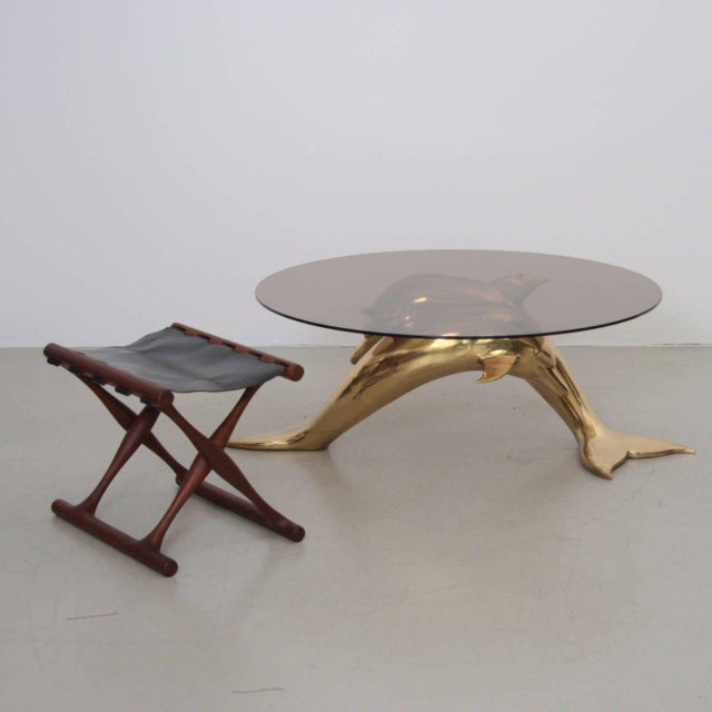 Very elegant and huge coffee table in brass and glass. The glass table top is holded by two brass dolphins. The table is a...