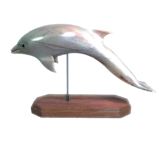A 3 piece collection of decorative figurines and sculpted fish effigies. 1. Wood Dolphin: hand sculpted and presented on a...