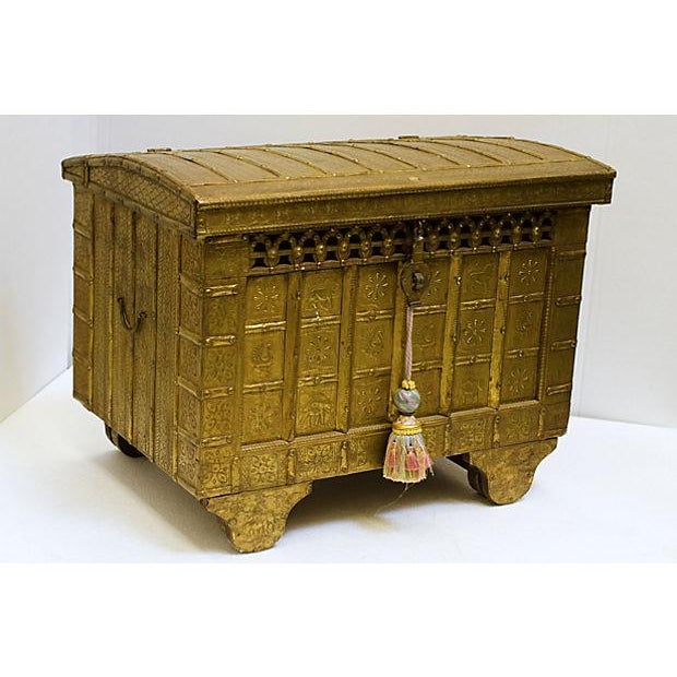 """A repoussé and incised brass and wood trunk with intricate details. 29"""" L x 21"""" W x 23"""" H."""