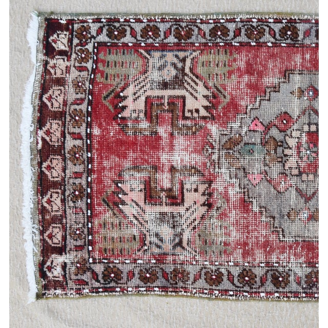 Hand-knotted Turkish wool accent rug in wonderful muted reds, creams and gray hues. Some wear consistent with age/use.
