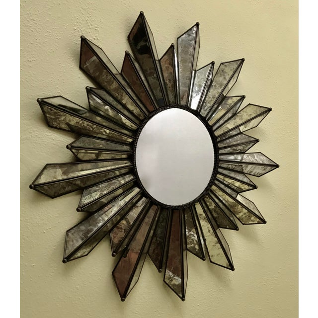 Soleil or sunburst wall mirror crafted from brass and antiqued mirror panels creating rays. Two rings of finely twisted...