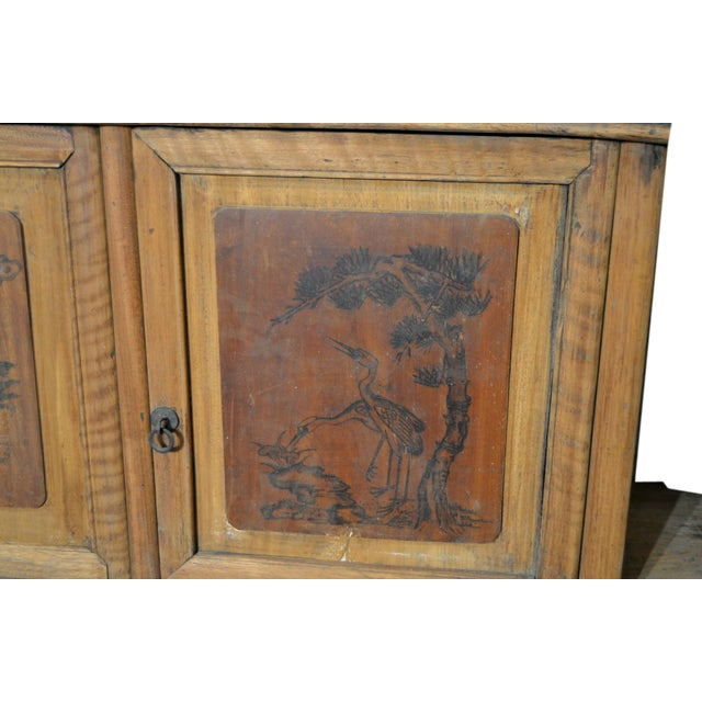 A Chinese 19th century four-door wooden low cabinet with hand-painted scenes. This long low cabinet features a rectangular...