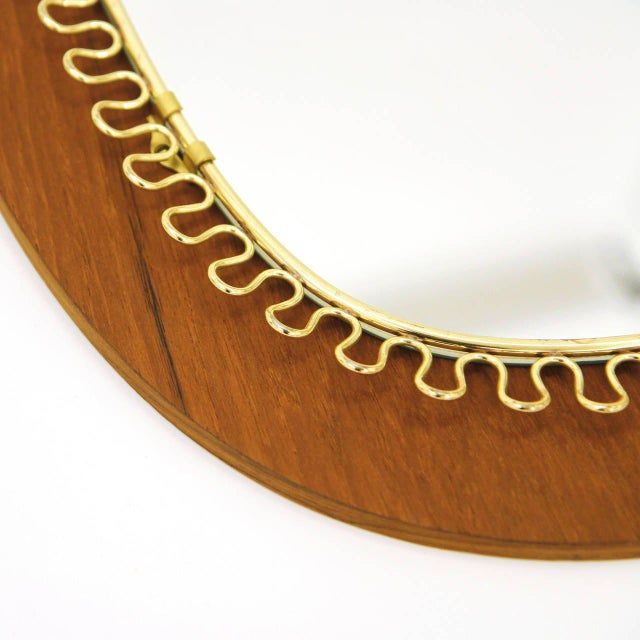 Rare version of Josef Frank's loop mirror with a teak backplate. Excellent condition with a nice patina on the brass.