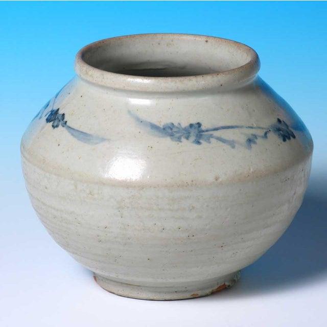Korean ceramic storage jar, thickly potted with slanted shoulder decorated in under glaze cobalt blue of blossoming...