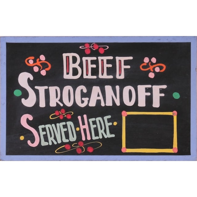 """A vintage, one-sided, hand-painted sign on chipboard saying """"Beef Stroganoff""""."""