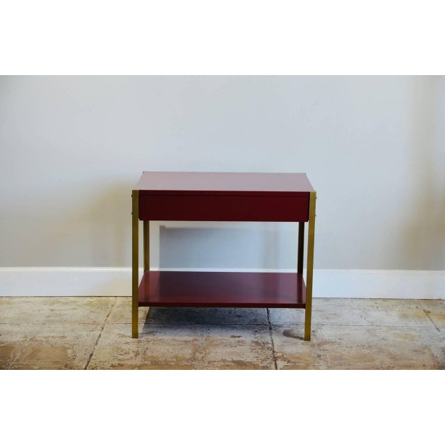 """Pair of high gloss 'Laque' oxblood lacquer and brass nightstands by Design Frères. Shelf height is 6"""" in."""