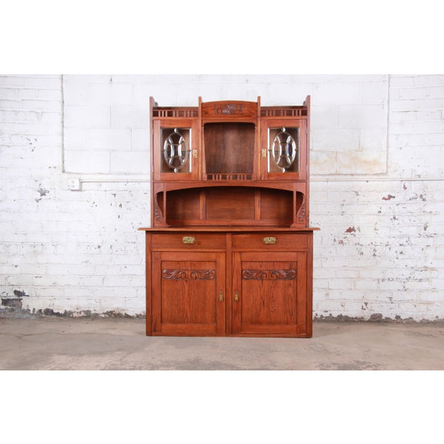 An exceptional Arts & Crafts carved oak bar cabinet or sideboard with hutch USA, Mid-20th Century Solid carved oak +...