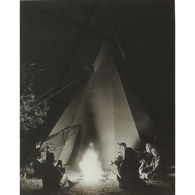 A historical photo of Native American figures around a campfire outside of a teepee. This reprint was done by Alex Blendl....