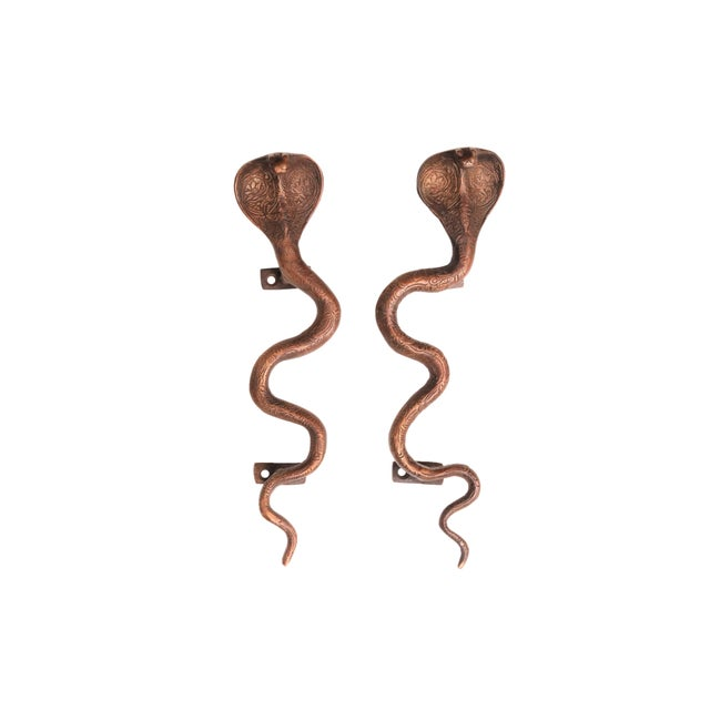 A pair of large antiqued dark brass cobra door handles or cabinet pulls. Hollywood Regency in style, with intricate...
