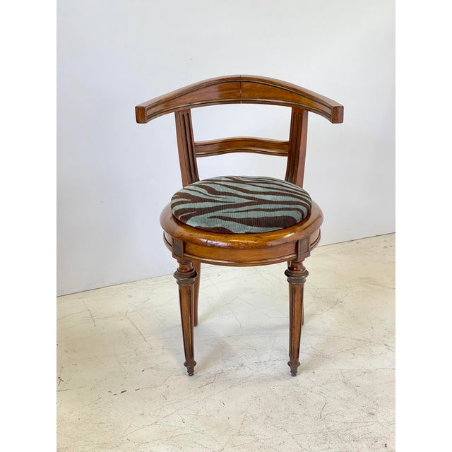 Early 20th Century Italian neoclassical vanity chair made of walnut with brass inlay. The round raised seat cushion is...