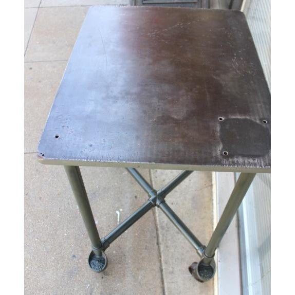 Old industrial table that was either originally used in a machine shop or print shop. Appears to have had a vice bolted to...