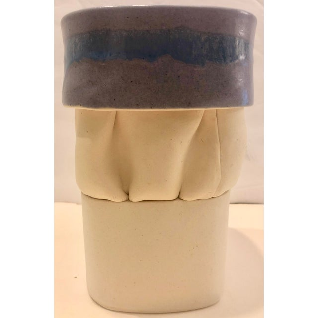 Artistic pottery vase in a mat cream color with purple glaze. Interesting shape and texture. Signed on bottom.