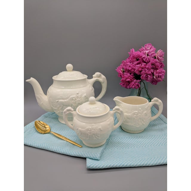 This lovely set includes the teapot, creamer, and sugar bowl made by Wedgwood in England in the late 20th century....