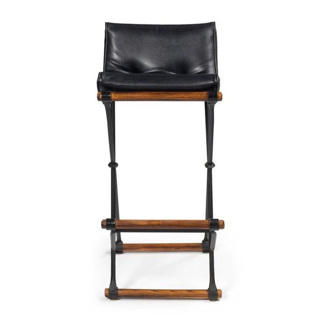 A set of five wrought iron X fame bar stools with oak stretchers and loose seat button tufted cushions. In the casual...