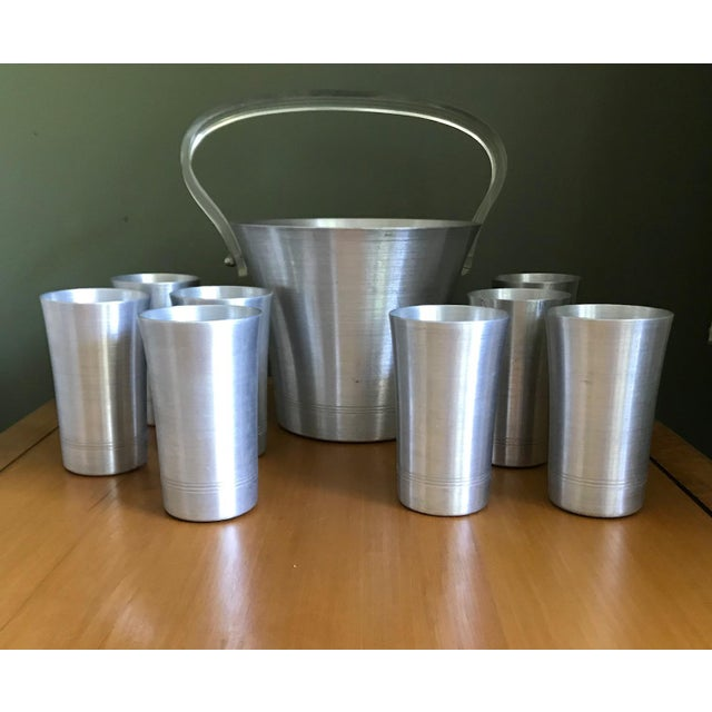 Vintage 1970's aluminum ice bucket with Lucite handle. The set incluses 8 matching glasses. All pieces are hand turned by...