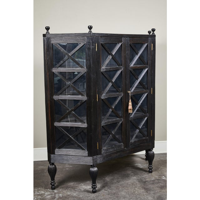 A 20th century British Colonial solid ebony two door display cabinet, from Sri Lanka.