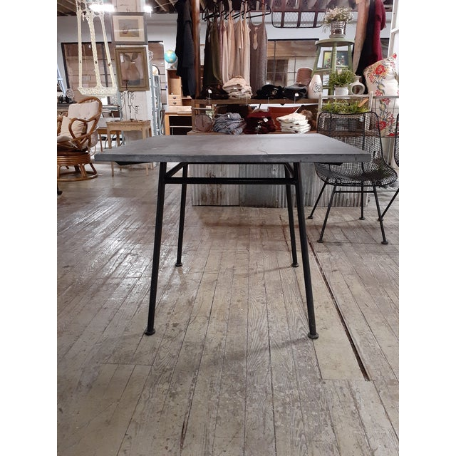 Very rare original slate top patio or poolside table by Woodard. Wrought iron base accompanied by four Woodard Sculptura...