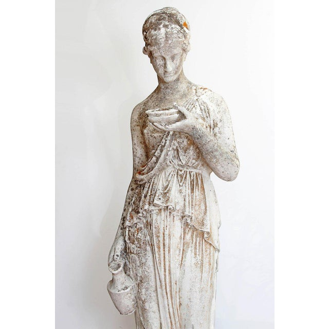 A 19th century French hand carved stone life-sized statue of a classical maiden holding a jug and a bowl. Historically,...