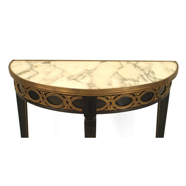 French 1940s (Louis XVI style) ebonized demilune shaped console table with a bronze scroll design apron under an inset...