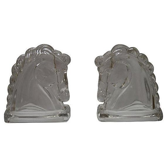 """Clear glass horse-head bookends. Measures 4.25"""" L x 3"""" D x 5.5"""" H"""