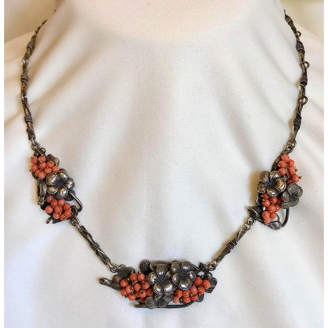 C1930 sterling silver necklace with ornate floral motif links set with natural coral beads and suspended from an ornately...