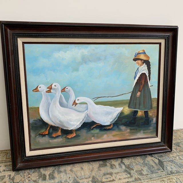 This is an absolutely precious signed oil on canvas painting of a village girl herding geese. It comes in a beautiful wood...