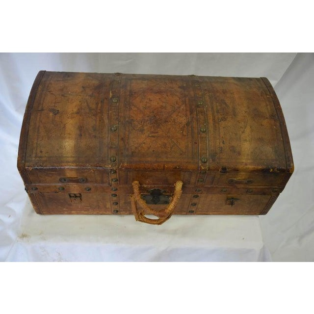 Antique travel dome trunk shipping luggage case in distressed vintage leather. Fabulous toile fabric lined interior. With...