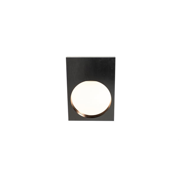 Rose-tinted round mirror with a wood frame in ebony or custom-finish. Made in USA.