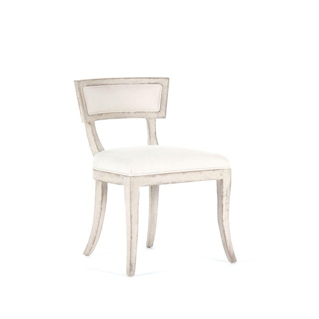 Side chair with linen upholstery, four curved legs, padded back, and foam filling.