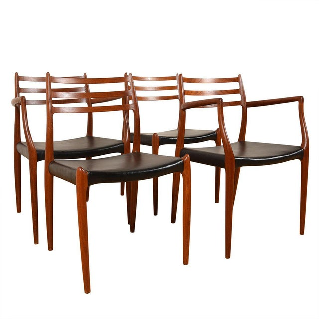 This is a set of 4 Danish Modern dining chairs designed by Niels Moller, in teak with black seats. This set includes two...