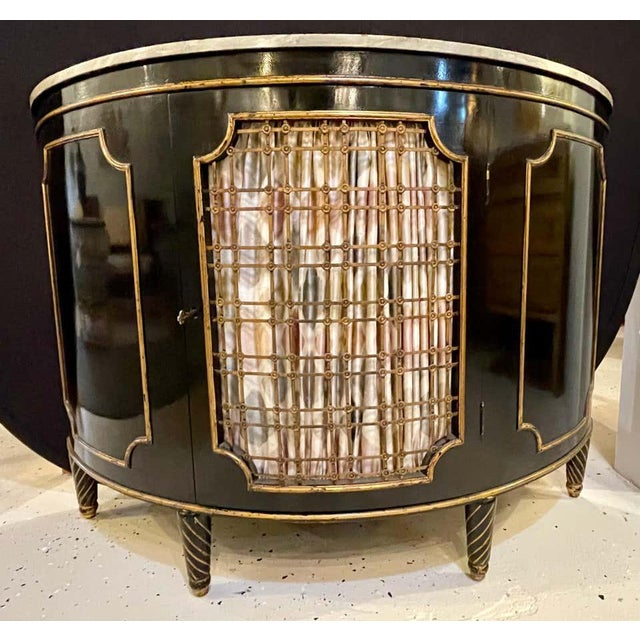 A demilune commode or server gilt gold and bronze decorated, Hollywood Regency style commode, chest or nightstand that is...