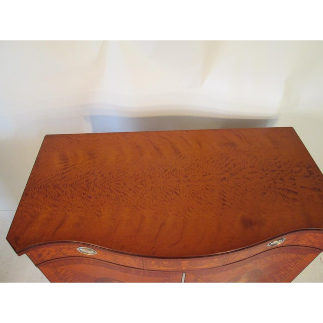 This is a chest made by Schmieg and Kotzian made in NY NY. The chest is made of satinwood. The front of the chest is a...