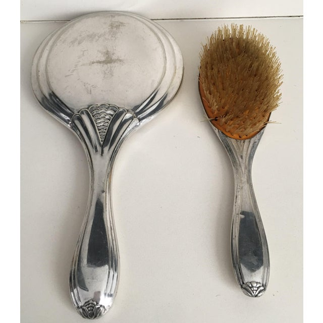 About A beautiful Victorian period sterling silver hand mirror and brush, French, circa 1890 with ornamental decoration....