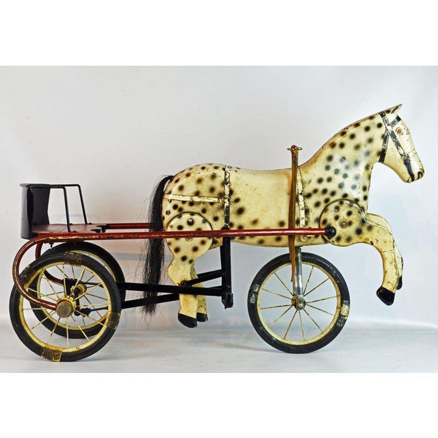 This sulky style pedal tricycle features a seat supported by two wheels and an intriguing tole horse mounted on the front...