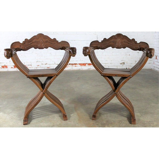Gorgeous carved Savonarola style pair of chairs in walnut with lion heads for the arm ends. This is a vintage circa 20th...
